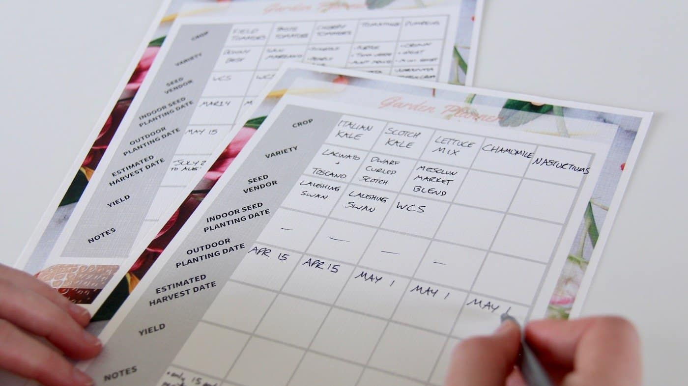 garden planner with hand filling in pages for organic garden planning