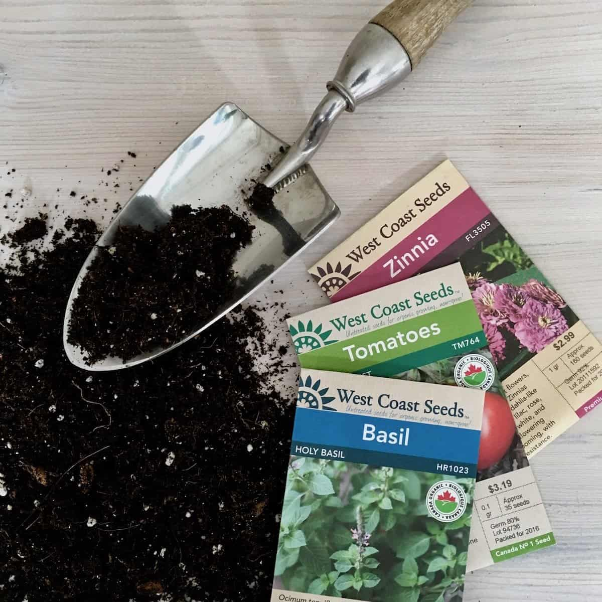 seed packets and potting soil with garden trowel for seeds for sale