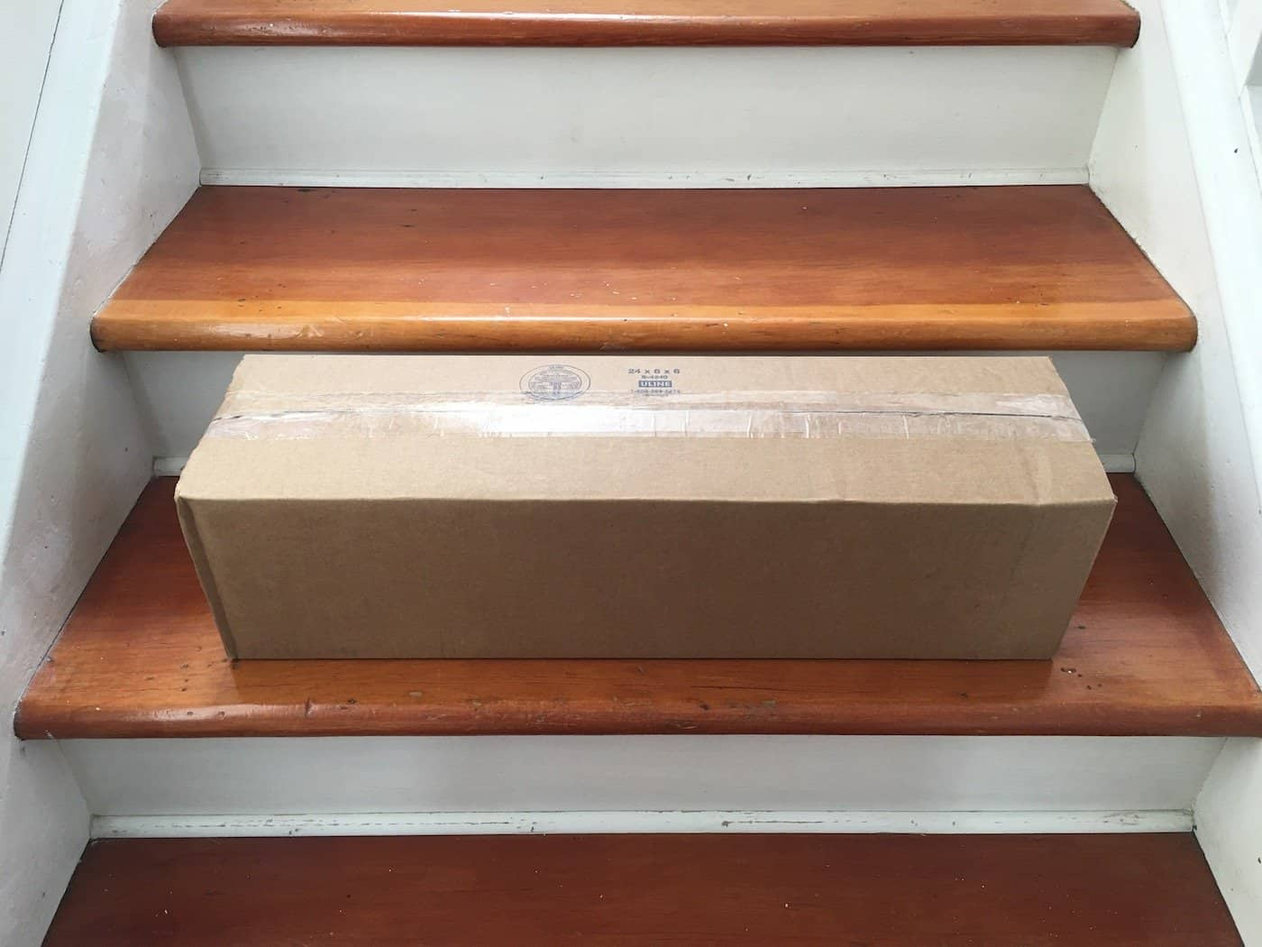 shipping box on stairs full of plants bought online