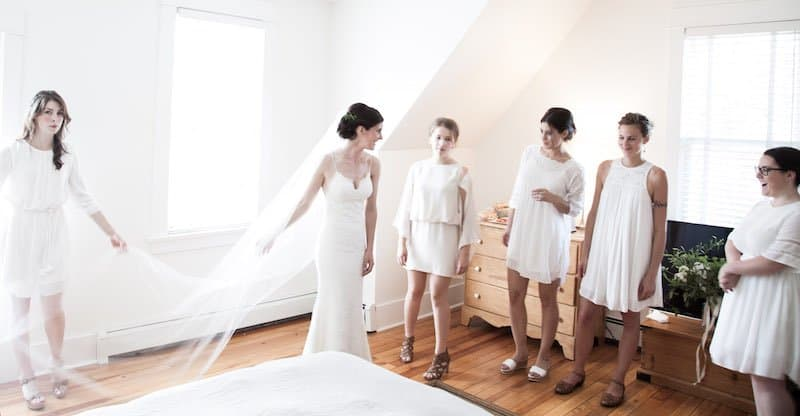 bridal party all dressed in white getting ready for a wedding ceremony in a heritage home