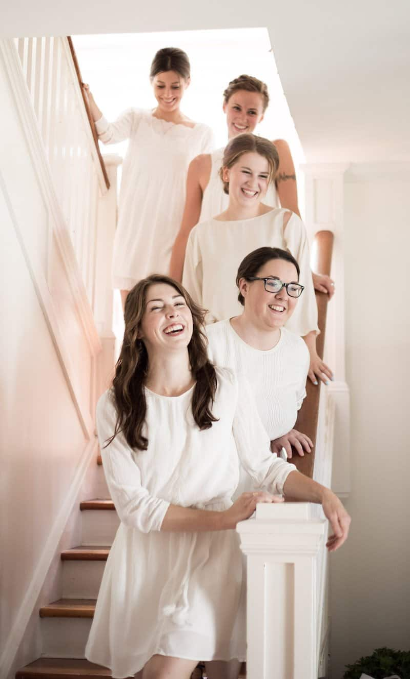five bridesmaids in white dresses smiling on white staircase at wedding reception at home