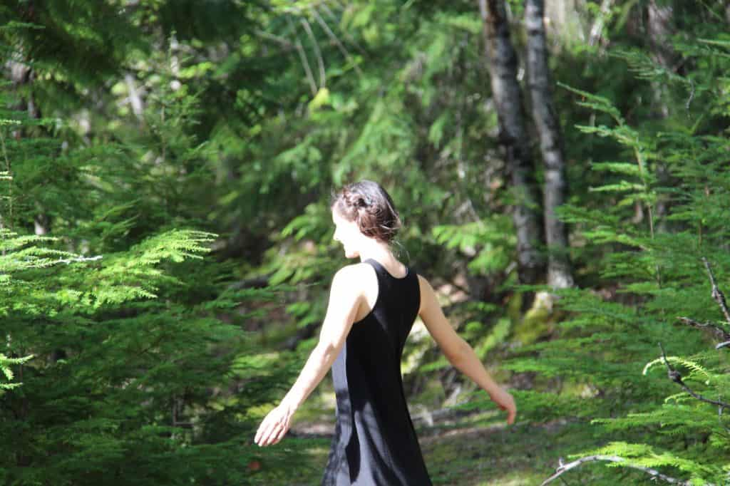 woman in black dress forest bathing in a forest of evergreen trees