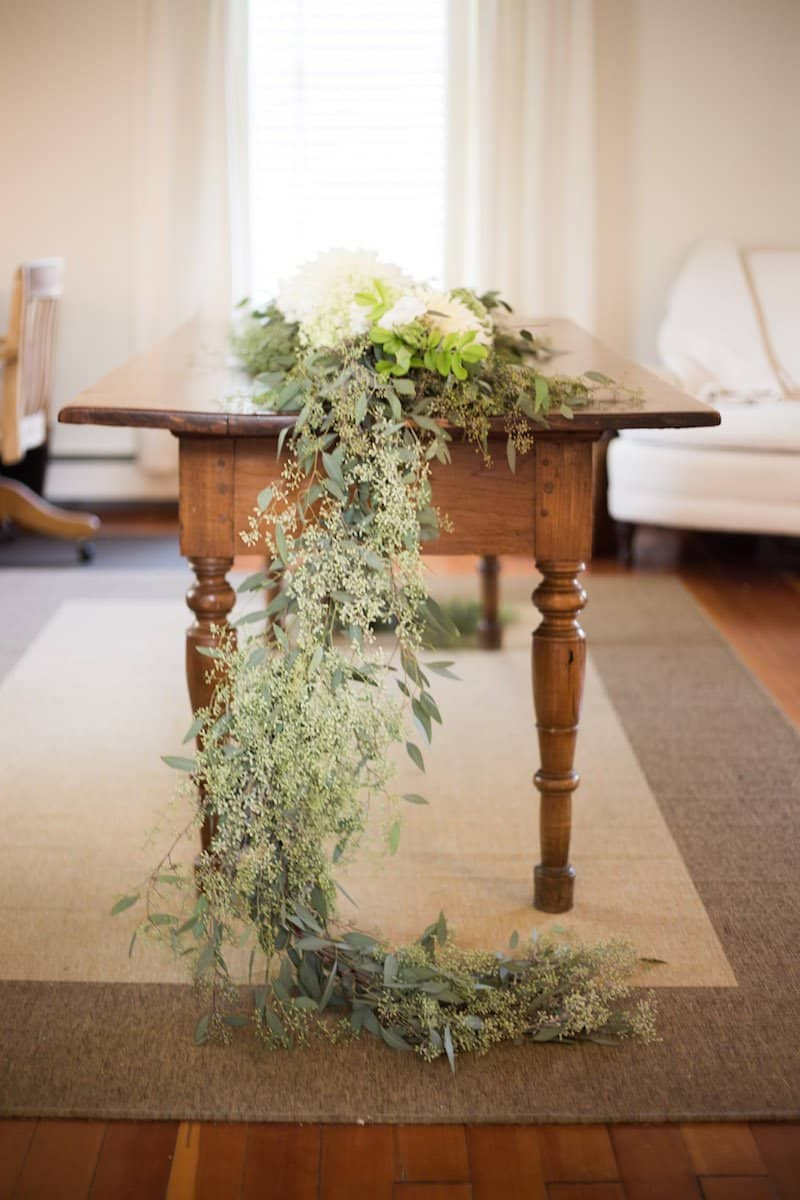 wooden table with wedding greenery foliage table runner made with eucalyptus and white cafe au lait dahlias in a white room