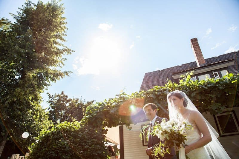bride walking down the aisle at a garden party wedding ceremony at home