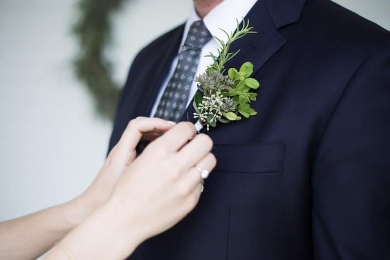 green herb boutonniere with rosemary and eucalyptus being pinned onto dark navy suit