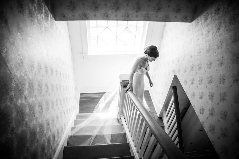 bride walking down stairs to wedding ceremony at home in an old house