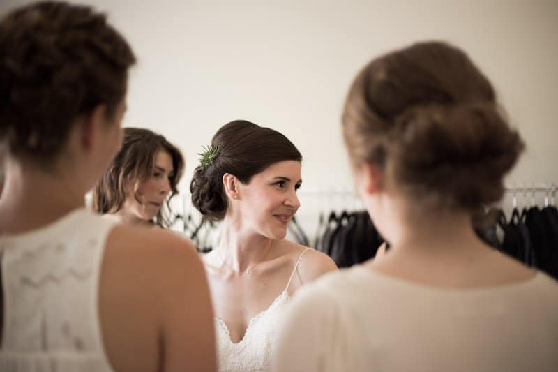 brunette bridal updo hairstyle with small sprig of rosemary greenery for a woodsy wedding