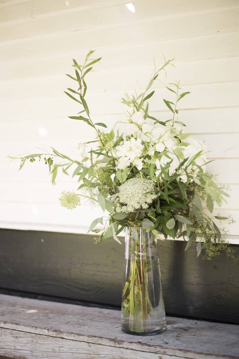 simple green foliage bridal bouquet with eucalyptus, queen anne's lace, and other white flowers on a garden bench