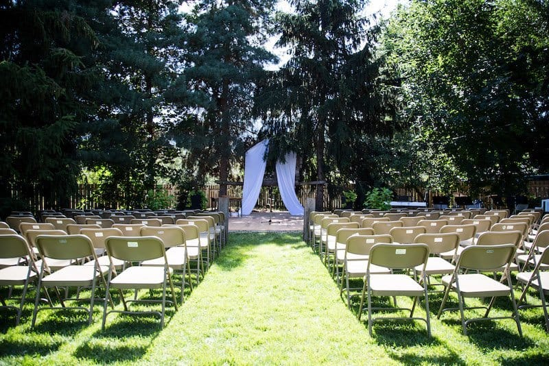 chairs and wedding altar set up for a backyard wedding ceremony on green grass with woodsy evergreen trees in the background