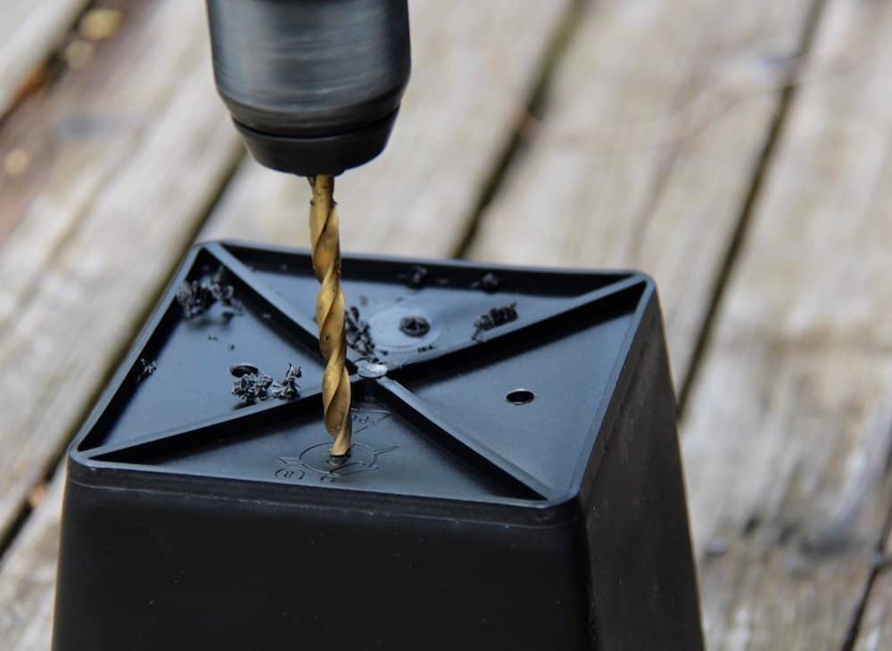 drill drilling holes into the bottom of a black plastic herb garden planter