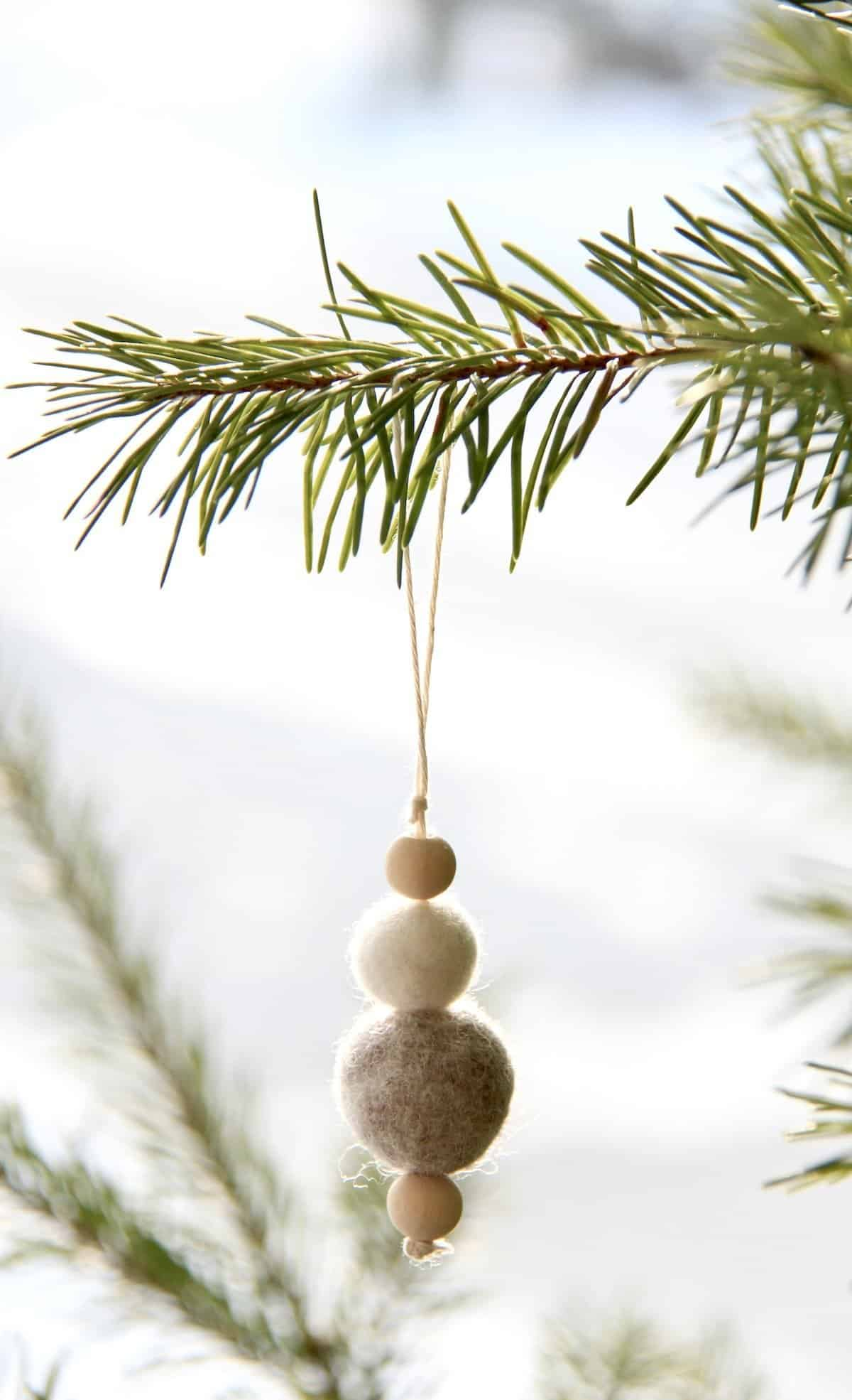 felt ball ornament with wooden beads on natural christmas tree