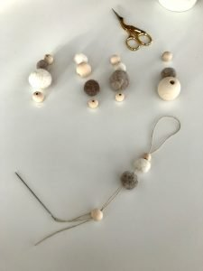 making felt ball ornaments with wooden beads and thin embroidery floss