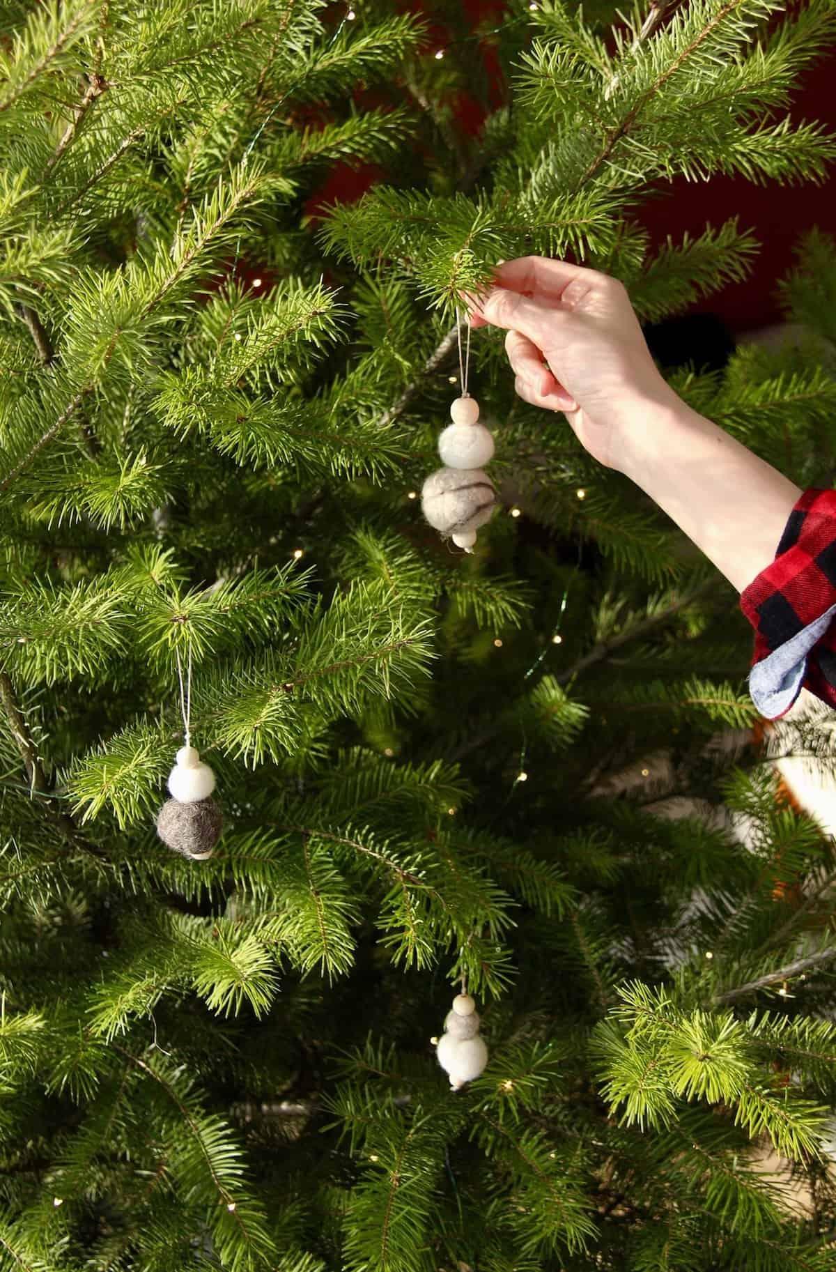 hanging felt ball ornaments on the christmas tree