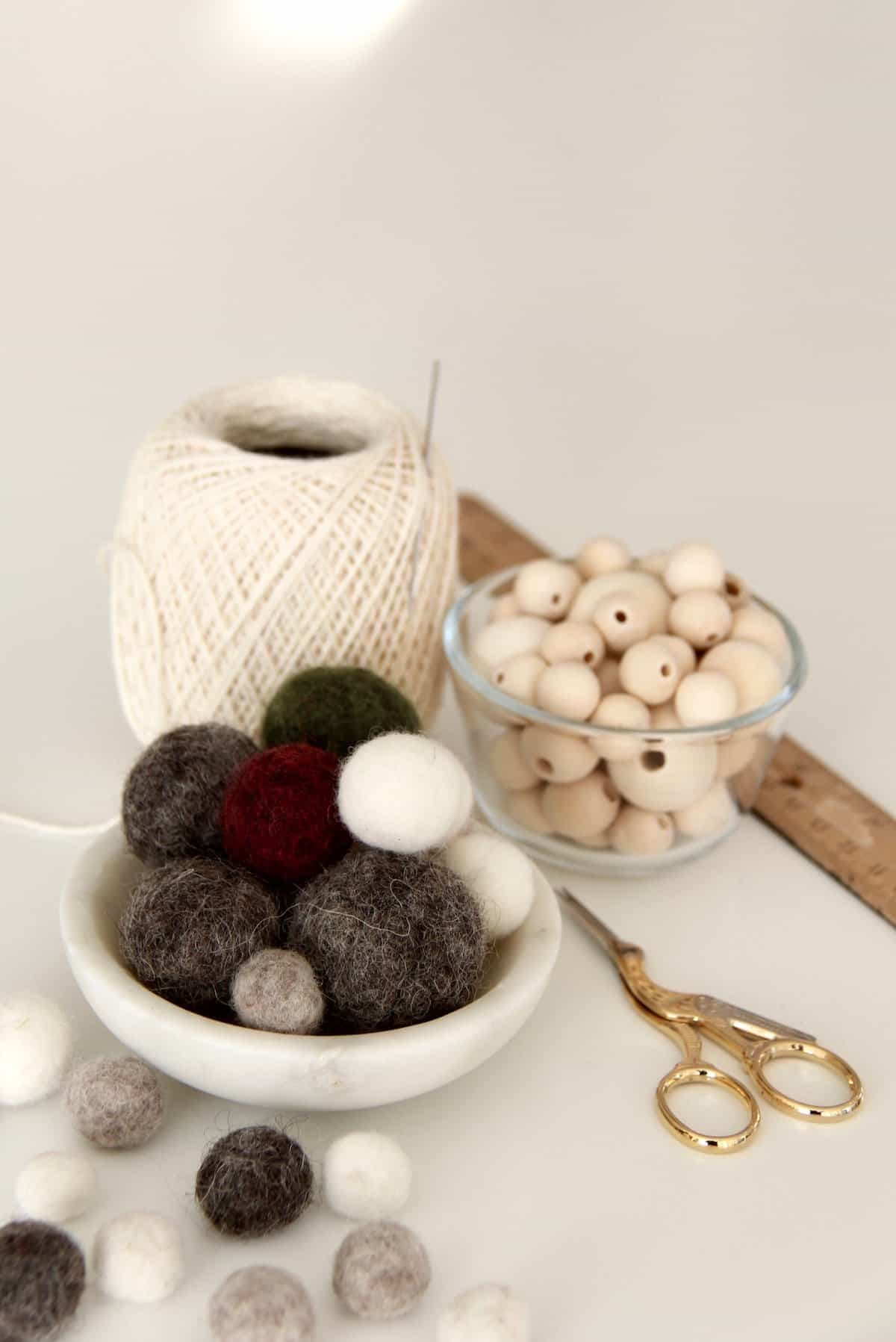 Handmade grey, green, and white wool felt balls in a small bowl, along with wooden beads, string, and sewing scissors