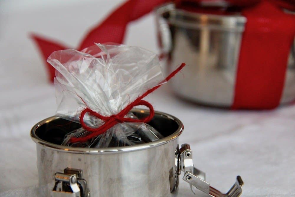 Small metal food container holding small plastic bag tied with red bow