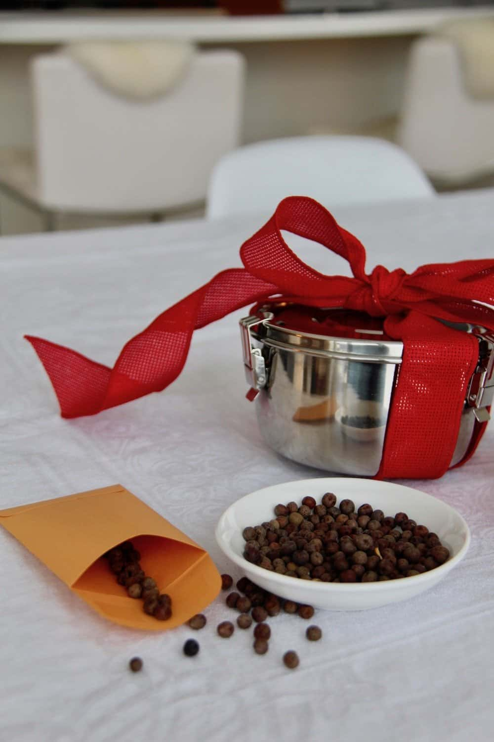 Metal food container wrapped in red bow with seeds on a dish and in an envelope