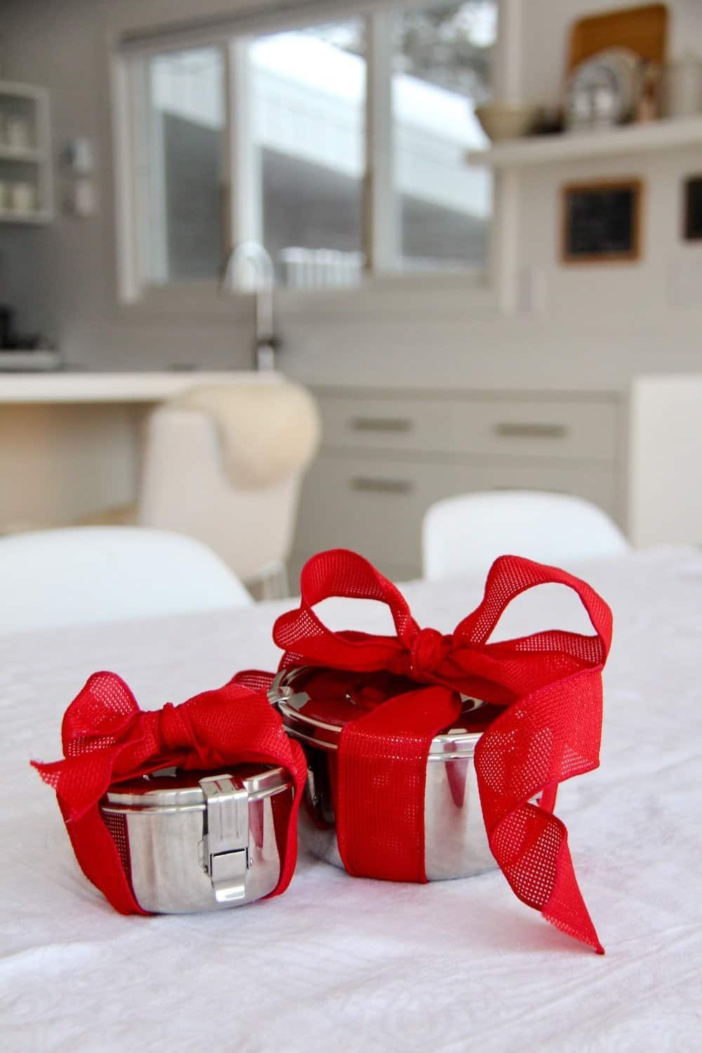 Two round micro green containers wrapped in red valentines ribbon for a DIY Valentines gift