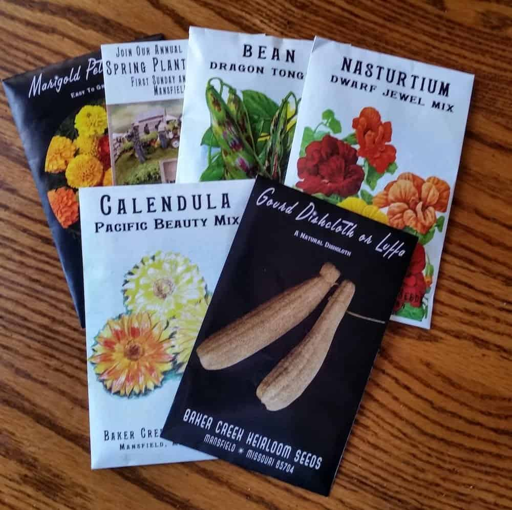 baker creek non gmo seed packets full of vegetable seeds and flower seeds on a wooden table