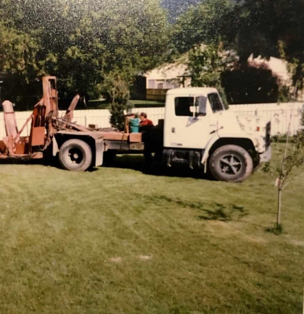 Tree spade machine planting trees in a backyard