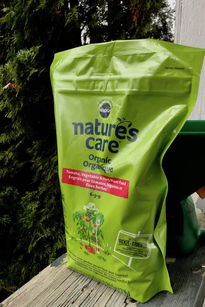 Organic Miracle Grow Bag on Front Porch with Fertilizer Spreader