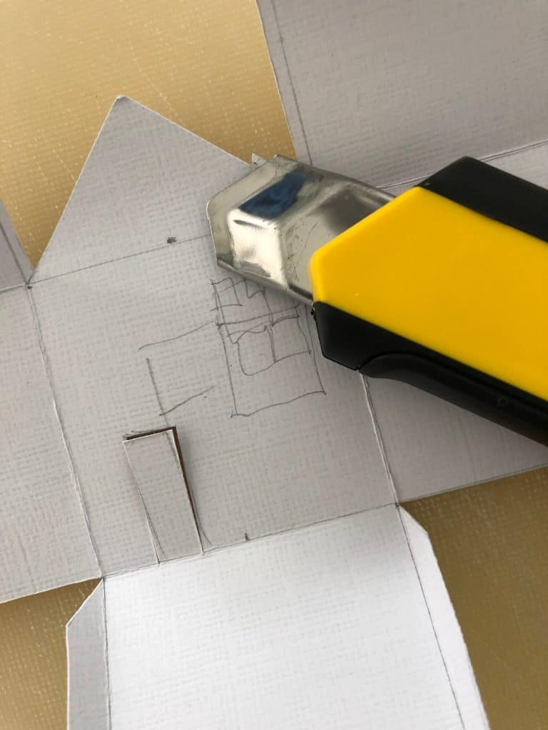 Cutting out the shape of the paper house