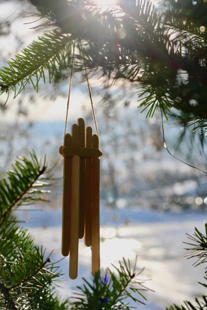 Popsicle Stick Sled Hanging on Christmas Tree in Sunlight with Snow