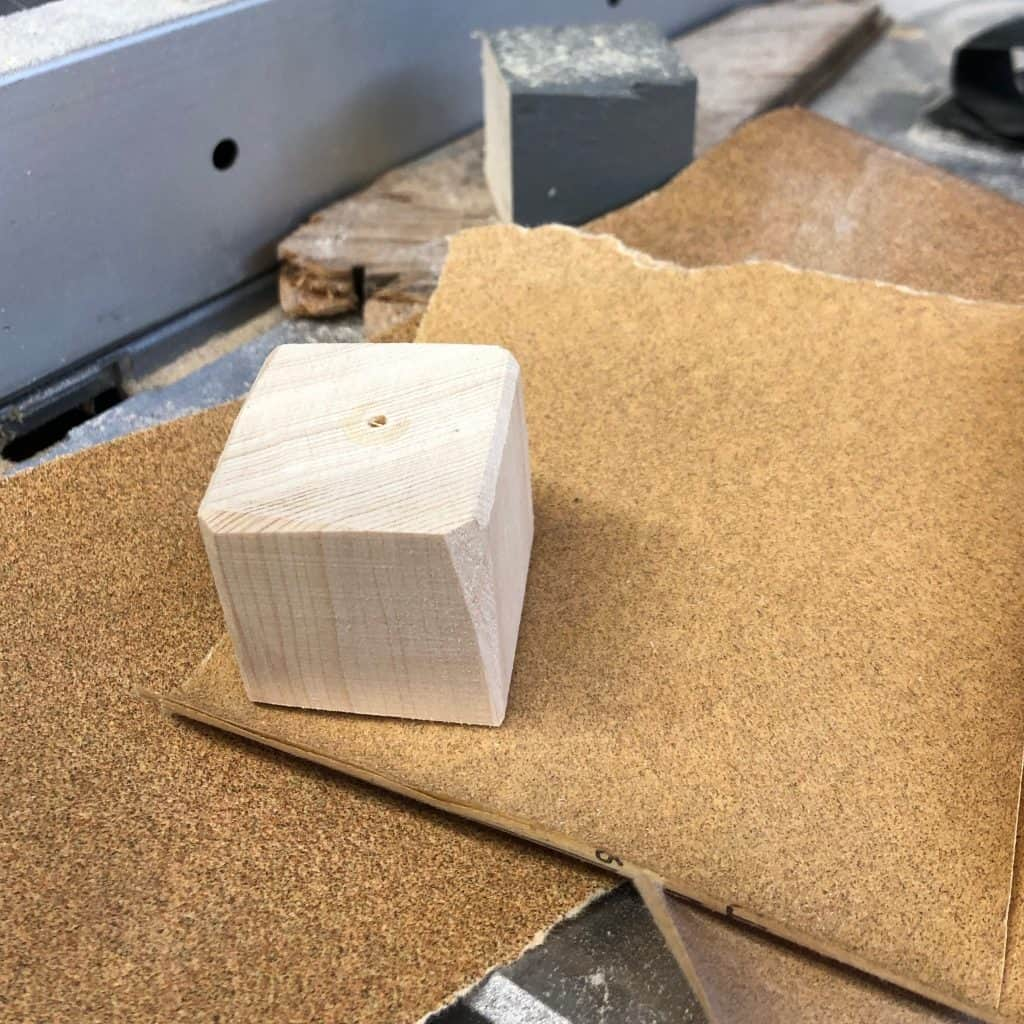 Sanding the edges on a wooden block cube before putting photos on it