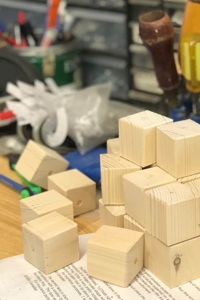 Stack of wooden blocks on workbench with ornament hanging holes drilled in them