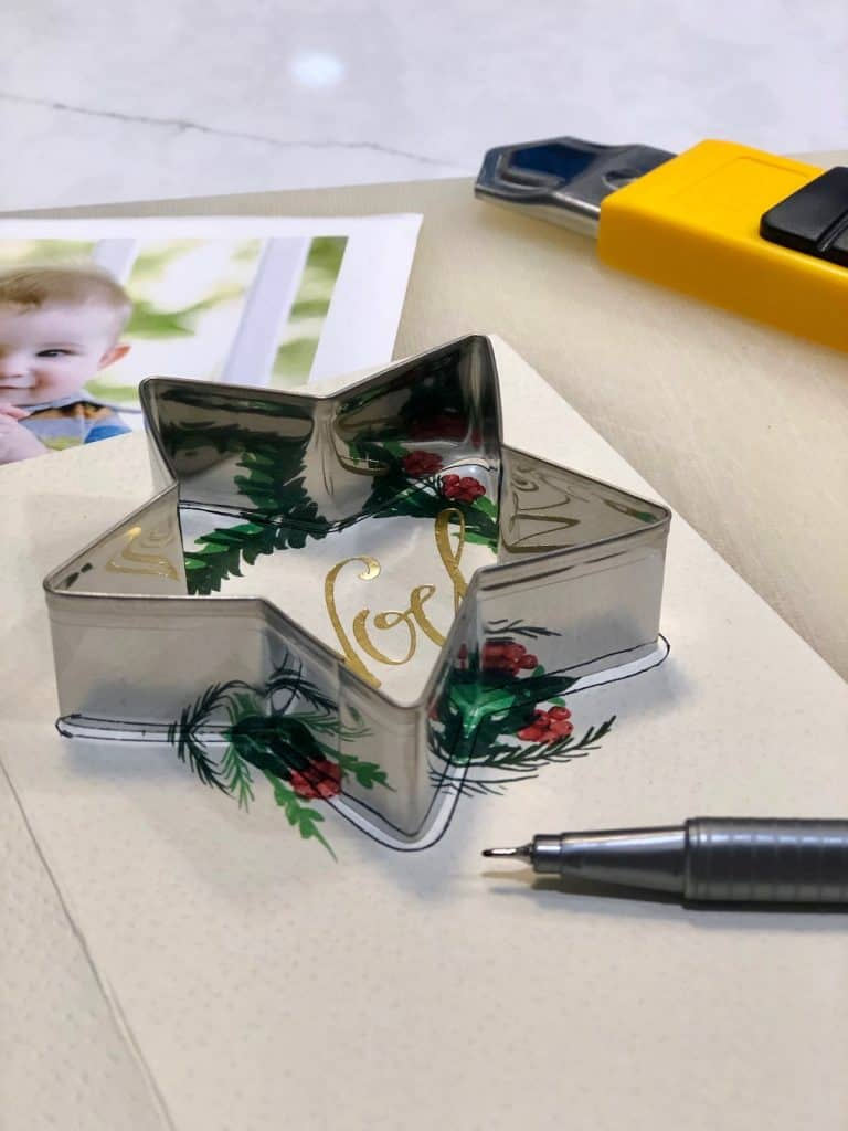 Using a cookie cutter to cut a Christmas card into a star shape