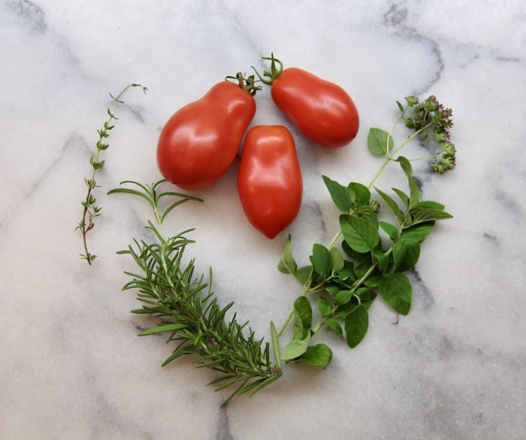 Italian San Marzano Tomatoes with Herbs on Marble Countertop