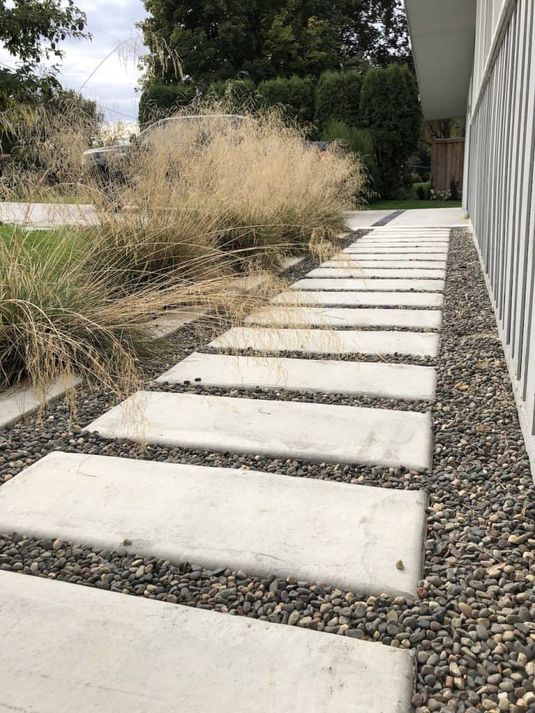 Pathway made from concrete rectangular paving stones and pea gravel