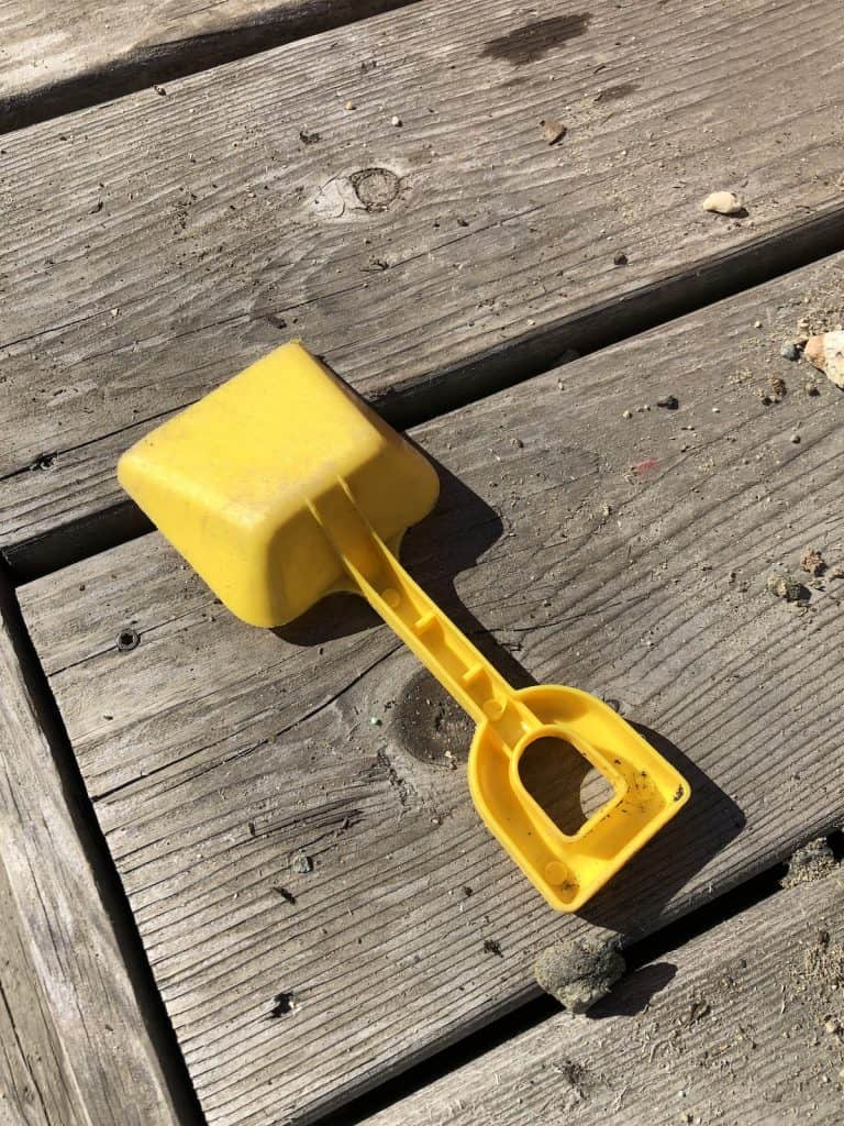 Plastic kids toy shovel - yellow - on wood patio outdoors