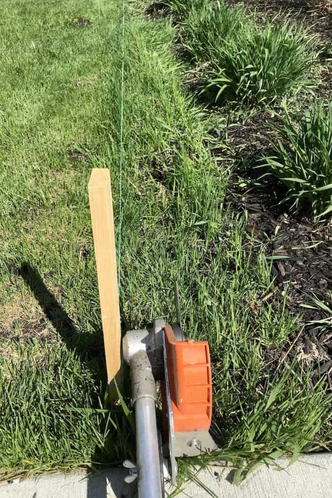 cutting a trench at the edge of a garden bed with stihl edger