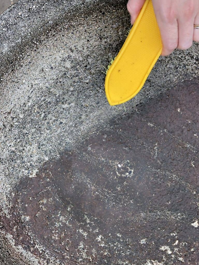 cleaning a concrete bird bath with a scrub brush