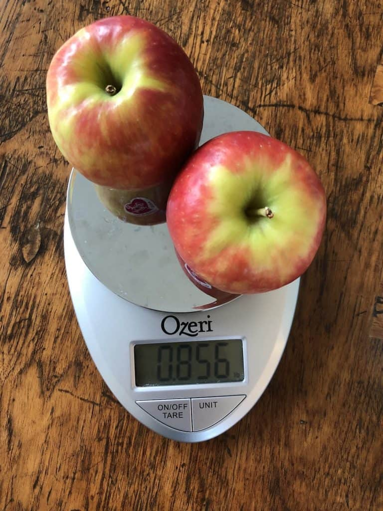 One pound of pink lady apples on a kitchen weigh scale