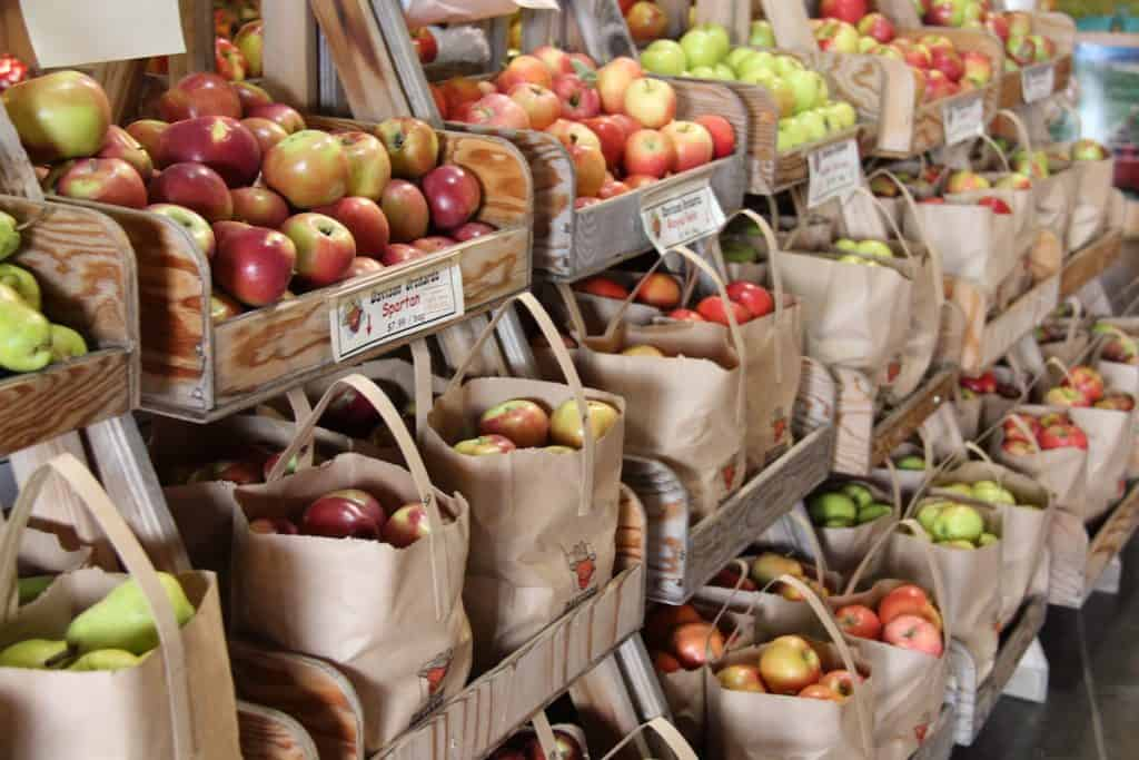 different types of apples in brown bags on wooden orchard shelves in store