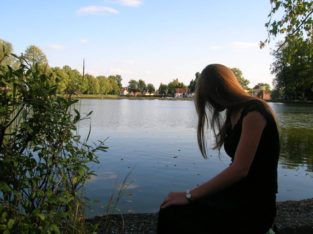 woman meditating in front of pond